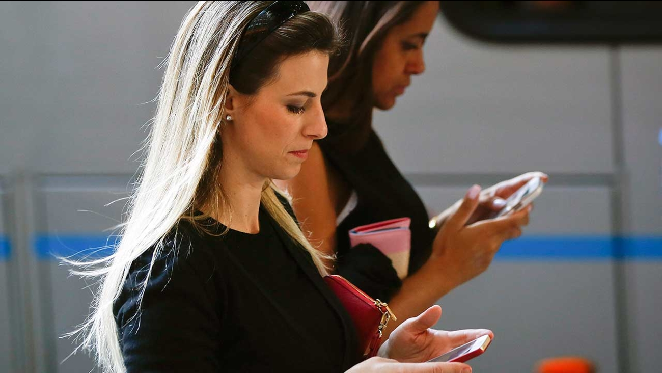 Women check their cellphones as they walk on the sidewalk.