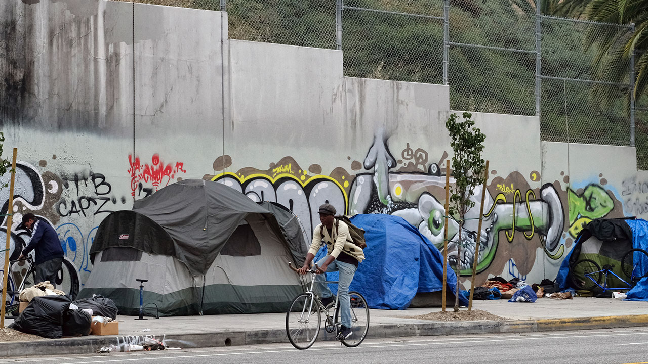 A cyclists rides past a homeless encampment alongside a street in downtown Los Angles on Wednesday, May 31, 2017.