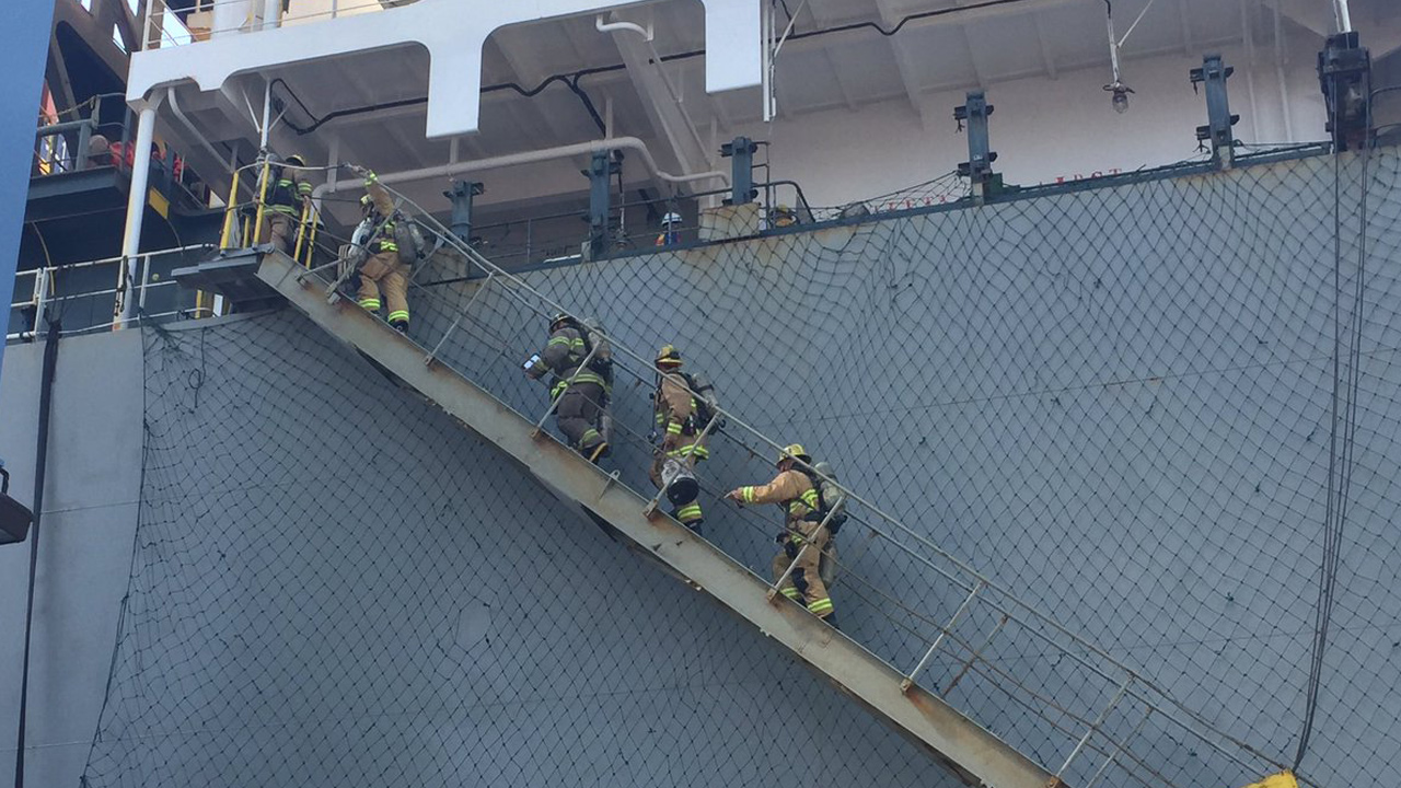 Firefighters board a ship in the Port of Long Beach after a hazardous chemical spill on Sunday, Aug. 6, 2017.