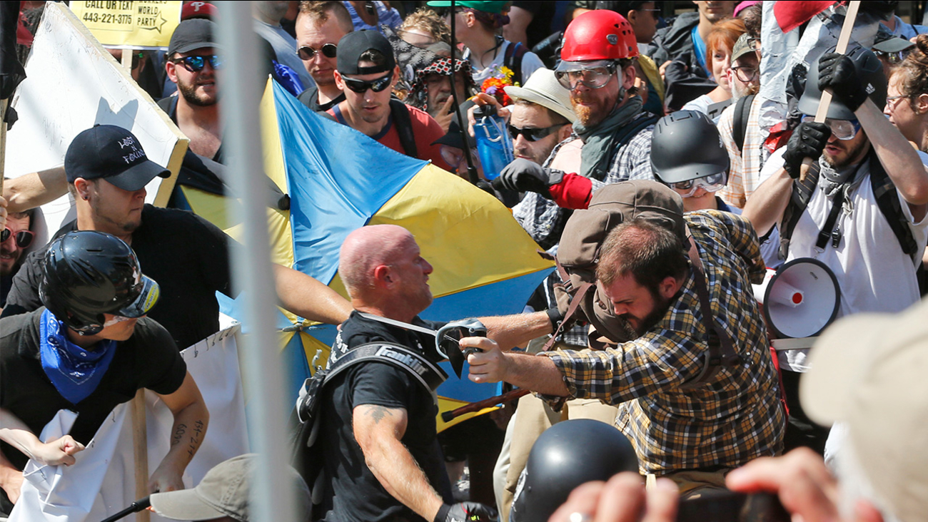 White nationalist demonstrators clash with counter demonstrators at the entrance to Lee Park in Charlottesville, Va., Saturday, Aug. 12, 2017.