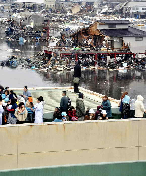 """<div class=""""meta image-caption""""><div class=""""origin-logo origin-image """"><span></span></div><span class=""""caption-text"""">People evacuated to a rooftop of a building look at other buildings damaged by tsunami tidal waves at a port in Kesennuma in Miyagi Prefecture, northern Japan, after strong earthquakes hit the area Friday, March 11, 2011. (AP Photo/Keichi Nakane, The Yomiuri Shimbun)</span></div>"""