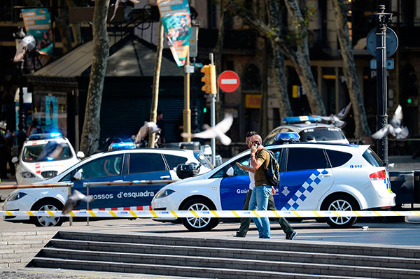 "<div class=""meta image-caption""><div class=""origin-logo origin-image none""><span>none</span></div><span class=""caption-text"">Plain-clothes policemen phone as they walk past police cars in a cordoned off area after a van plowed into a crowd, injuring pedestrians in Barcelona on August 17, 2017. (JOSEP LAGO/AFP/Getty Images)</span></div>"