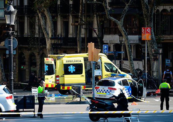 "<div class=""meta image-caption""><div class=""origin-logo origin-image none""><span>none</span></div><span class=""caption-text"">A policemen and a medical staff member stand past police cars and an ambulance in a cordoned off area after a van plowed into a crowd, injuring pedestrians in Barcelona. (JOSEP LAGO/AFP/Getty Images)</span></div>"
