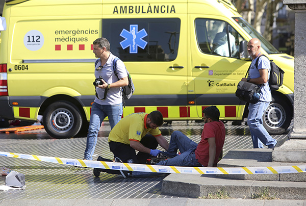 "<div class=""meta image-caption""><div class=""origin-logo origin-image none""><span>none</span></div><span class=""caption-text"">An injured person is treated in Barcelona after a white van jumped the sidewalk in the historic Las Ramblas district, crashing into a summer crowd of residents and tourists. (AP Photo/Oriol Duran)</span></div>"