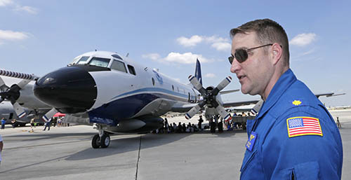 <div class='meta'><div class='origin-logo' data-origin='AP'></div><span class='caption-text' data-credit='AP Photo/Alan Diaz'>NOAA Lieutenant commander Nate Kahn, pilot of the NOAA Lockheed WP-3D Orion N42RF Hurricane Hunter shown, stands on the tarmac as he talks to reporters as guests tour the aircraft.</span></div>