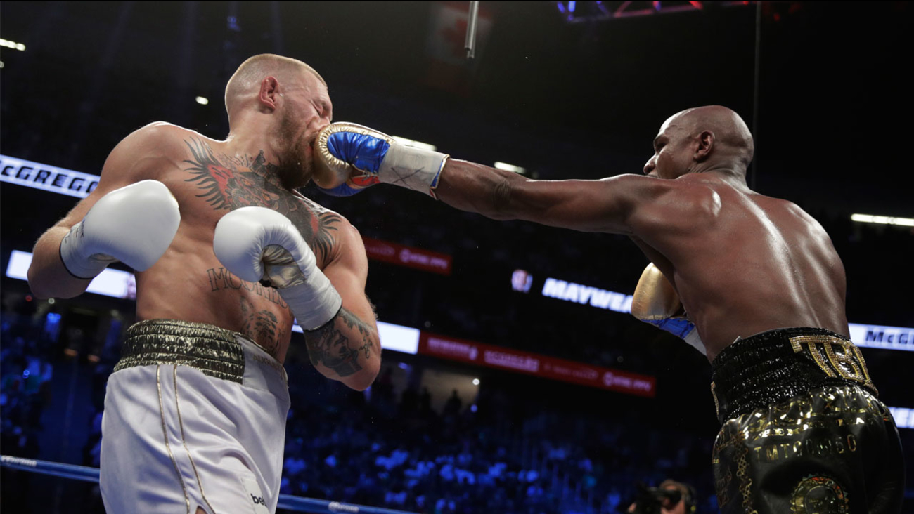 Floyd Mayweather Jr. jabs Conor McGregor in a super welterweight boxing match Saturday, Aug. 26, 2017, in Las Vegas.