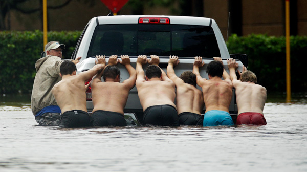 "<div class=""meta image-caption""><div class=""origin-logo origin-image none""><span>none</span></div><span class=""caption-text"">People push a stalled pickup through a flooded street in Houston, after Tropical Storm Harvey dumped heavy rains, Sunday, Aug. 27, 2017. (Charlie Riedel/AP Photo)</span></div>"