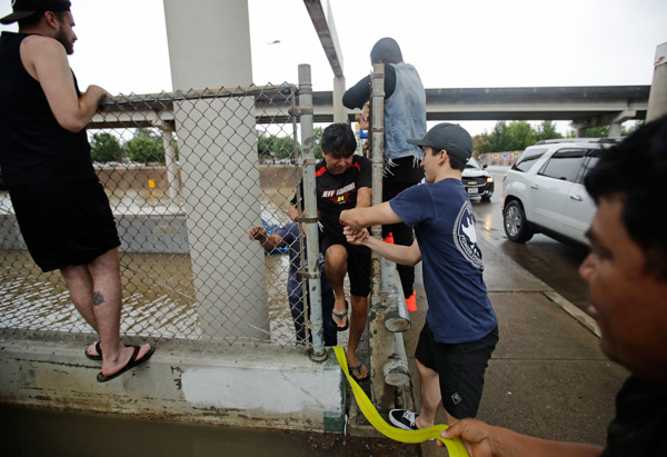 "<div class=""meta image-caption""><div class=""origin-logo origin-image none""><span>none</span></div><span class=""caption-text"">Carlos Torres, center, is helped through a fence after driving his tractor-trailer into a freeway flooded by Hurricane Harvey on Sunday, Aug. 27, 2017, near downtown Houston. (Charlie Riedel/AP)</span></div>"