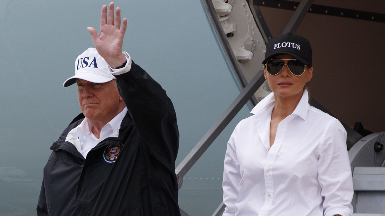 President Donald Trump, accompanied by first lady Melania Trump, waves as they arrive in Corpus Christi, Texas for briefings on Hurricane Harvey relief efforts.