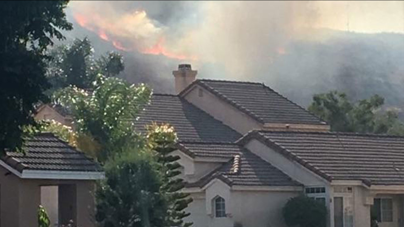 A photograph taken by an area resident showed flames and smoke adjacent to homes.