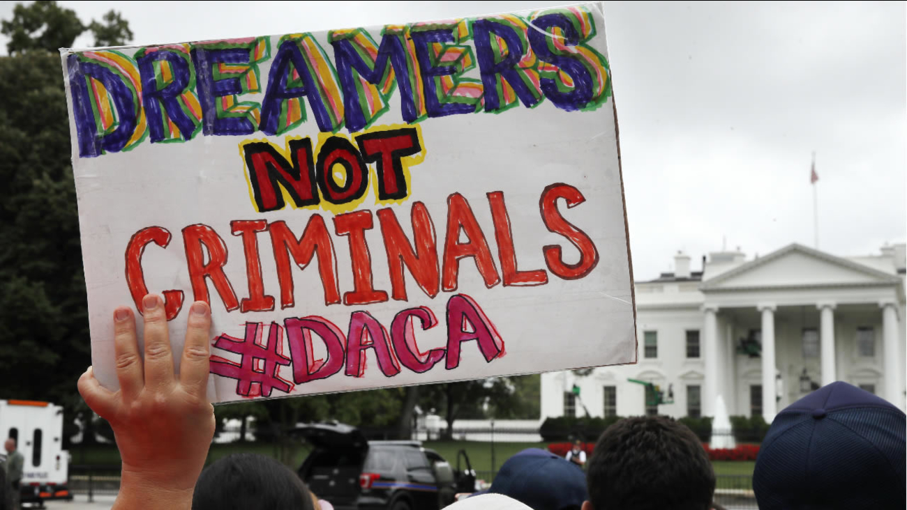 FILE- In this Aug. 15, 2017, a woman holds up a sign in support of the Obama administration program known as DACA during a rally at the White House in Washington. (AP Photo)