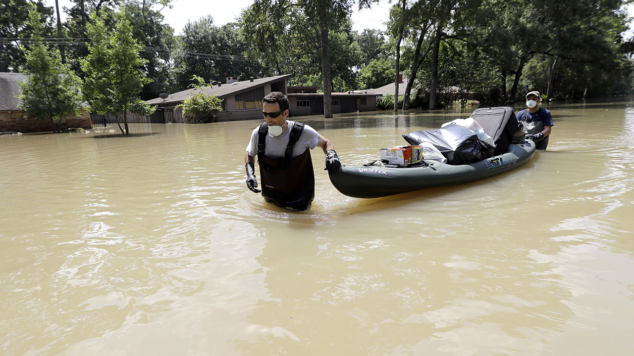 Gaston Kirby, left, is helped by friend Juan Minutella after gathering the last of his belongings from his flooded home in the aftermath of Hurricane Harvey Monday in Houston.