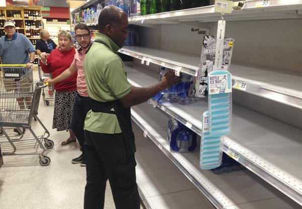 """<div class=""""meta image-caption""""><div class=""""origin-logo origin-image ap""""><span>AP</span></div><span class=""""caption-text"""">An employee restocks bottled water on bare shelves as customers look on at a Publix grocery store, Tuesday in Surfside, Fla. (Wilfredo Lee)</span></div>"""