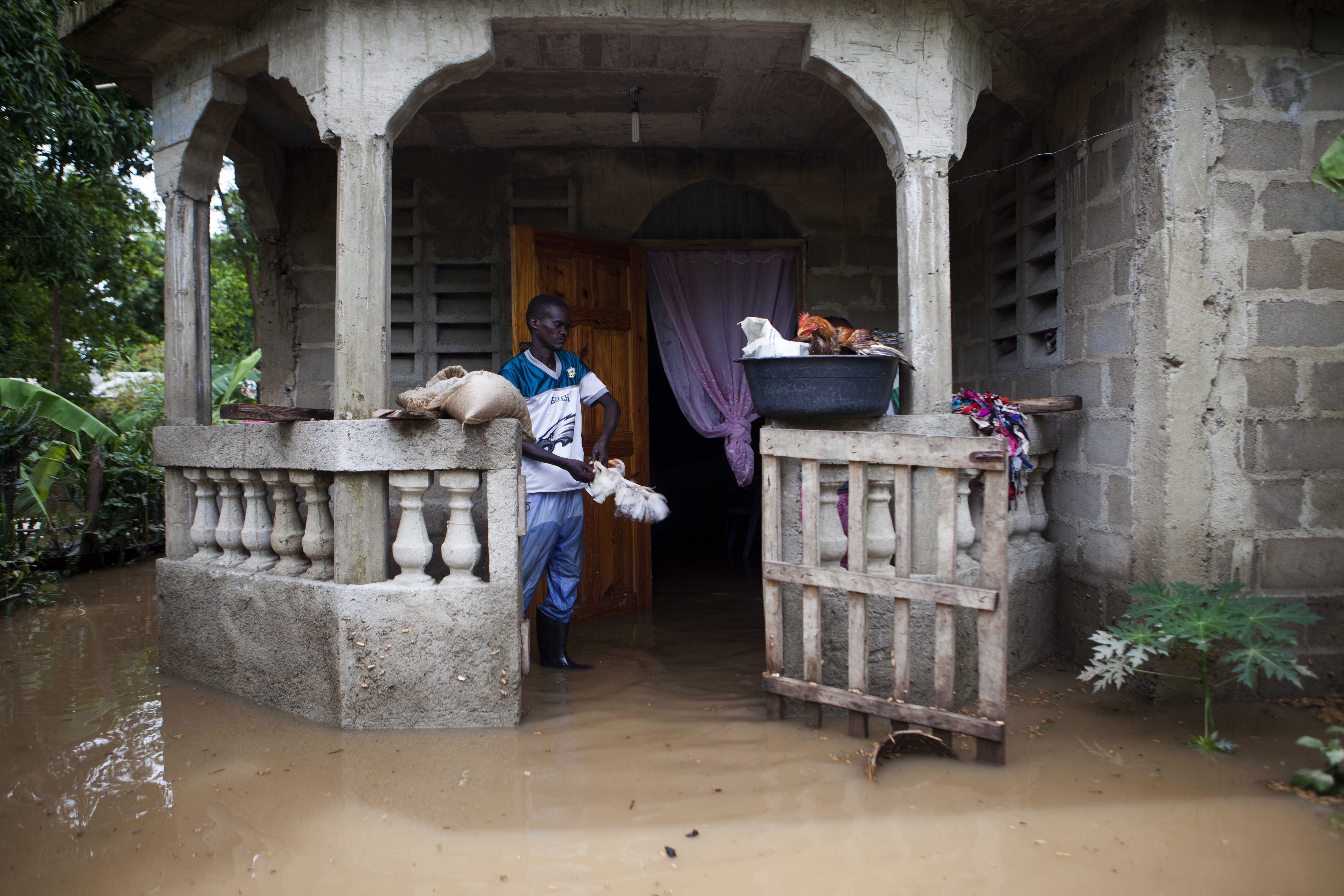 "<div class=""meta image-caption""><div class=""origin-logo origin-image none""><span>none</span></div><span class=""caption-text"">A man salvages items from his home flooded by heavy rains brought on by Hurricane Irma, in Fort-Liberte, Haiti, Friday Sept. 8, 2017. (Dieu Nalio Chery/AP Photo)</span></div>"