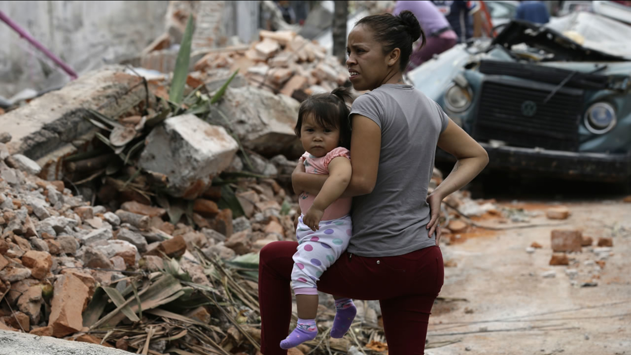 A woman holds her child as she stands next to wall turned to rubble when it collapsed during a massive earthquake, in Mexico City, Friday Sept. 8, 2017. (AP Photo/Marco Ugarte)