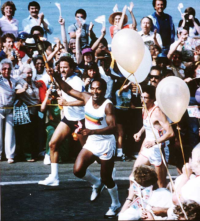 "<div class=""meta image-caption""><div class=""origin-logo origin-image ap""><span>AP</span></div><span class=""caption-text"">O.J. Simpson runs with the Olympic torch as the crowd cheers in downtown Los Angeles on July 21, 1984, one week before the opening ceremonies of the XXIII Summer Olympic Games. (AP Photo)</span></div>"