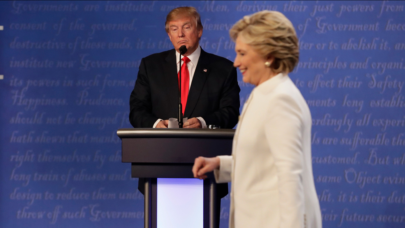 Republican presidential nominee Donald Trump waits behind his podium as Democratic presidential nominee Hillary Clinton makes her way off the stage.