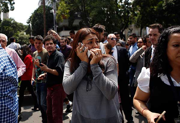 <div class='meta'><div class='origin-logo' data-origin='AP'></div><span class='caption-text' data-credit='AP Photo/Rebecca Blackwell'>A woman speaks on her cell phone as people evacuated from office building gather in Reforma Avenue after an earthquake in Mexico City, Tuesday Sept. 19, 2017.</span></div>