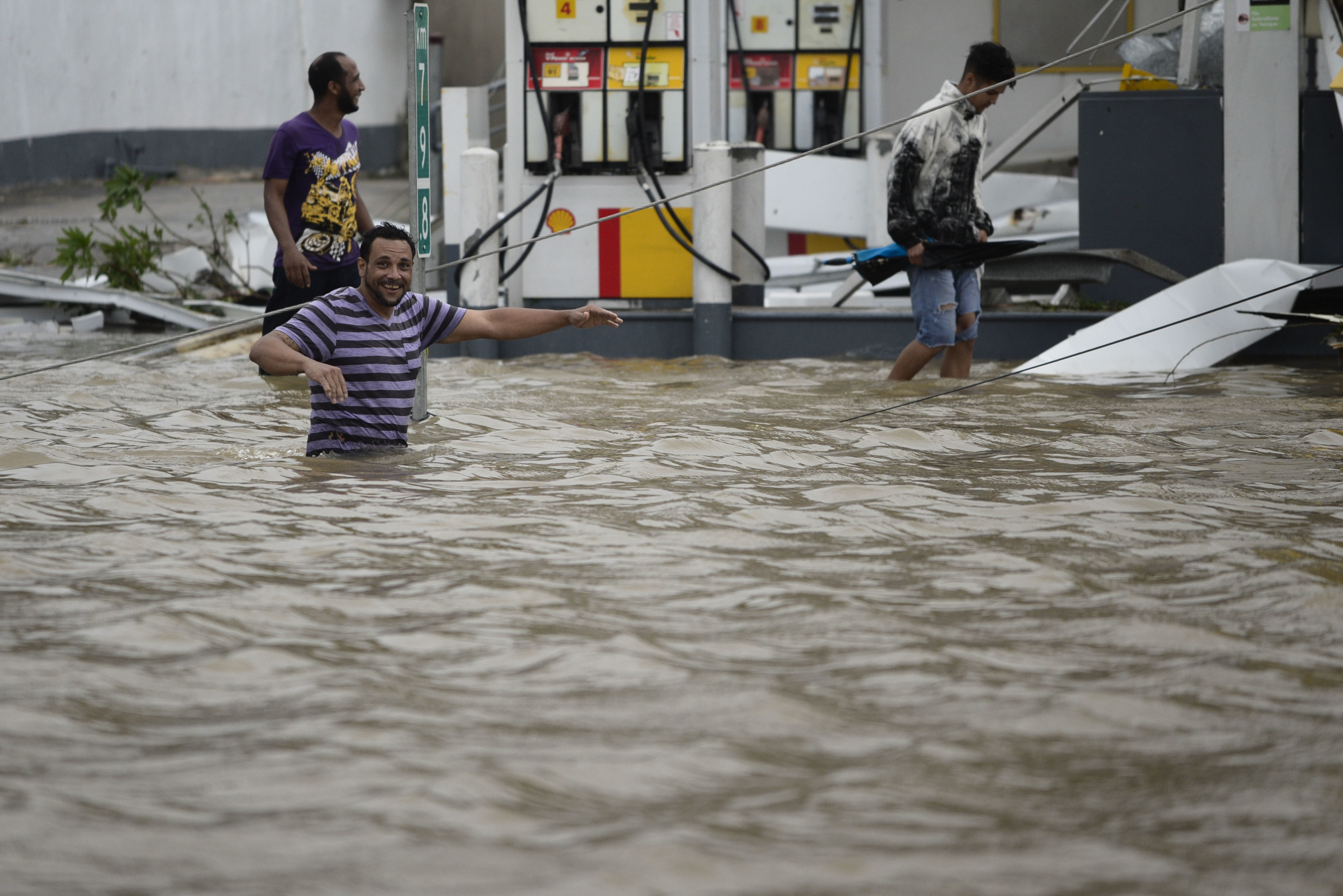 <div class='meta'><div class='origin-logo' data-origin='none'></div><span class='caption-text' data-credit='Carlos Giusti/AP Photo'>People walk next to a gas station flooded and damaged by the impact of Hurricane Maria in Puerto Rico, Wednesday, September 20, 2017.</span></div>
