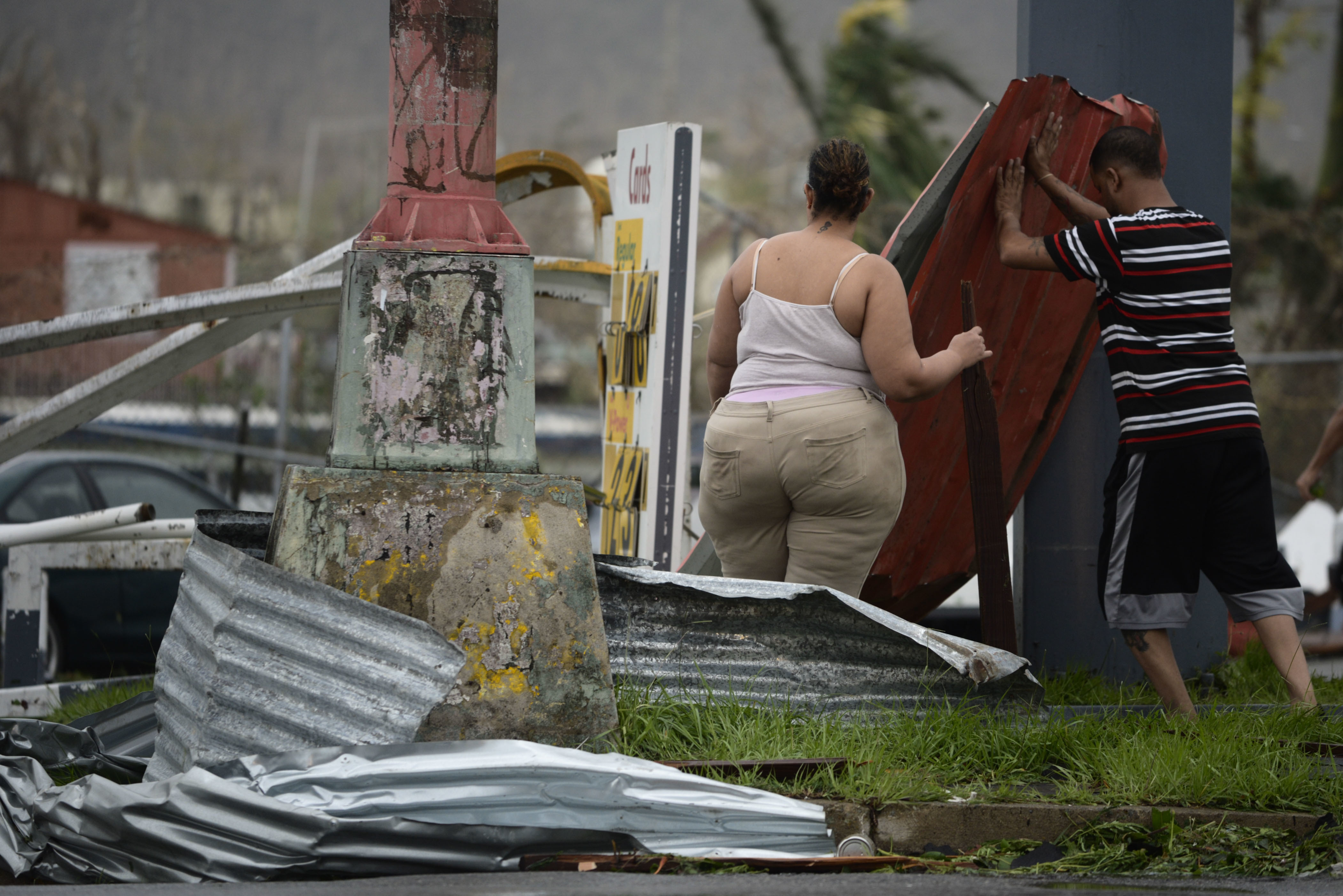 <div class='meta'><div class='origin-logo' data-origin='none'></div><span class='caption-text' data-credit='Carlos Giusti/AP Photo'>Residents move aluminum panels from an intersection after Hurricane Maria hit the eastern region of the island, in Humacao, Puerto Rico, Wednesday, Sept. 20, 2017.</span></div>