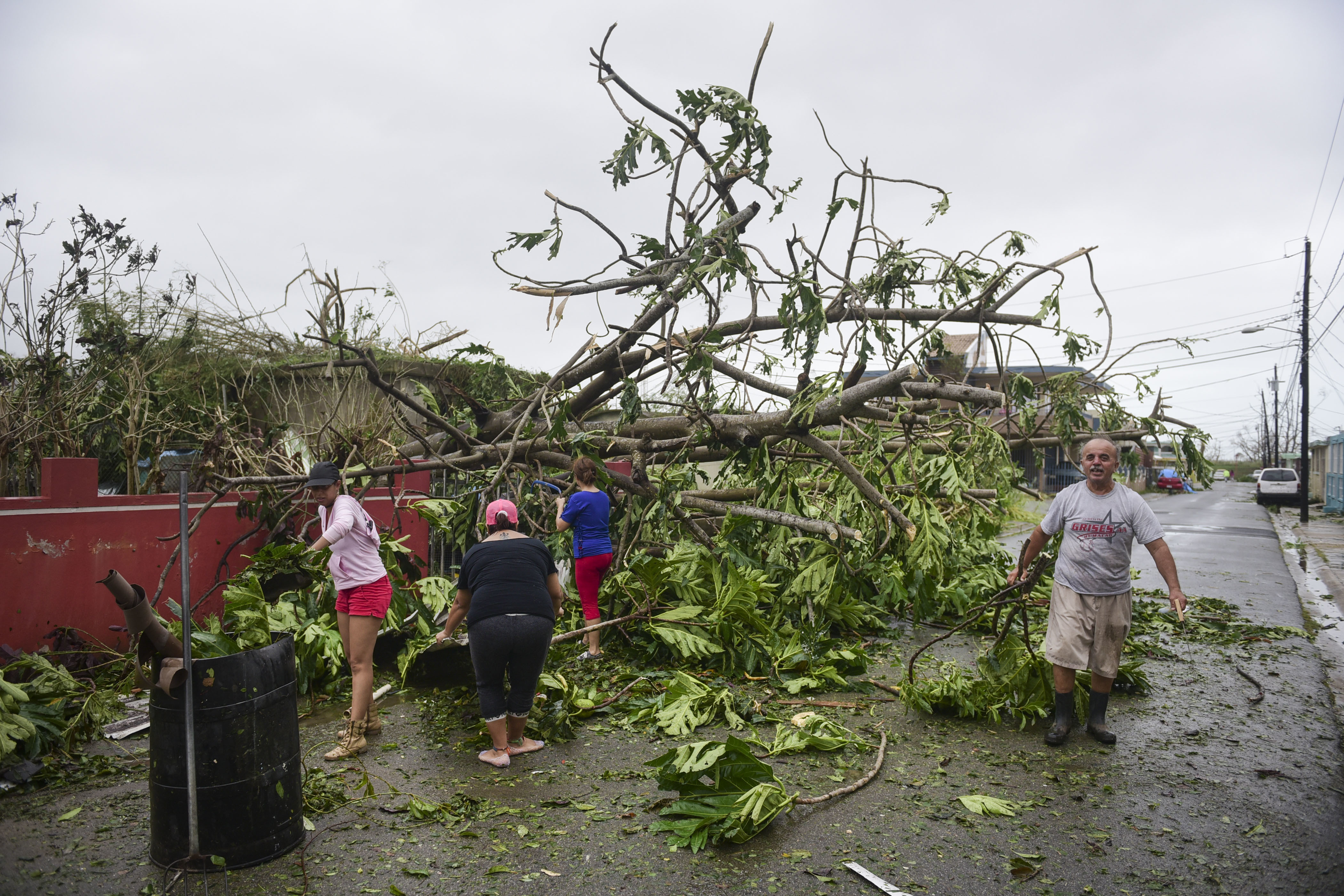 <div class='meta'><div class='origin-logo' data-origin='none'></div><span class='caption-text' data-credit='Carlos Giusti/AP Photo'>A family helps clean the road after Hurricane Maria hit the eastern region of the island, in Humacao, Puerto Rico, September 20, 2017.</span></div>