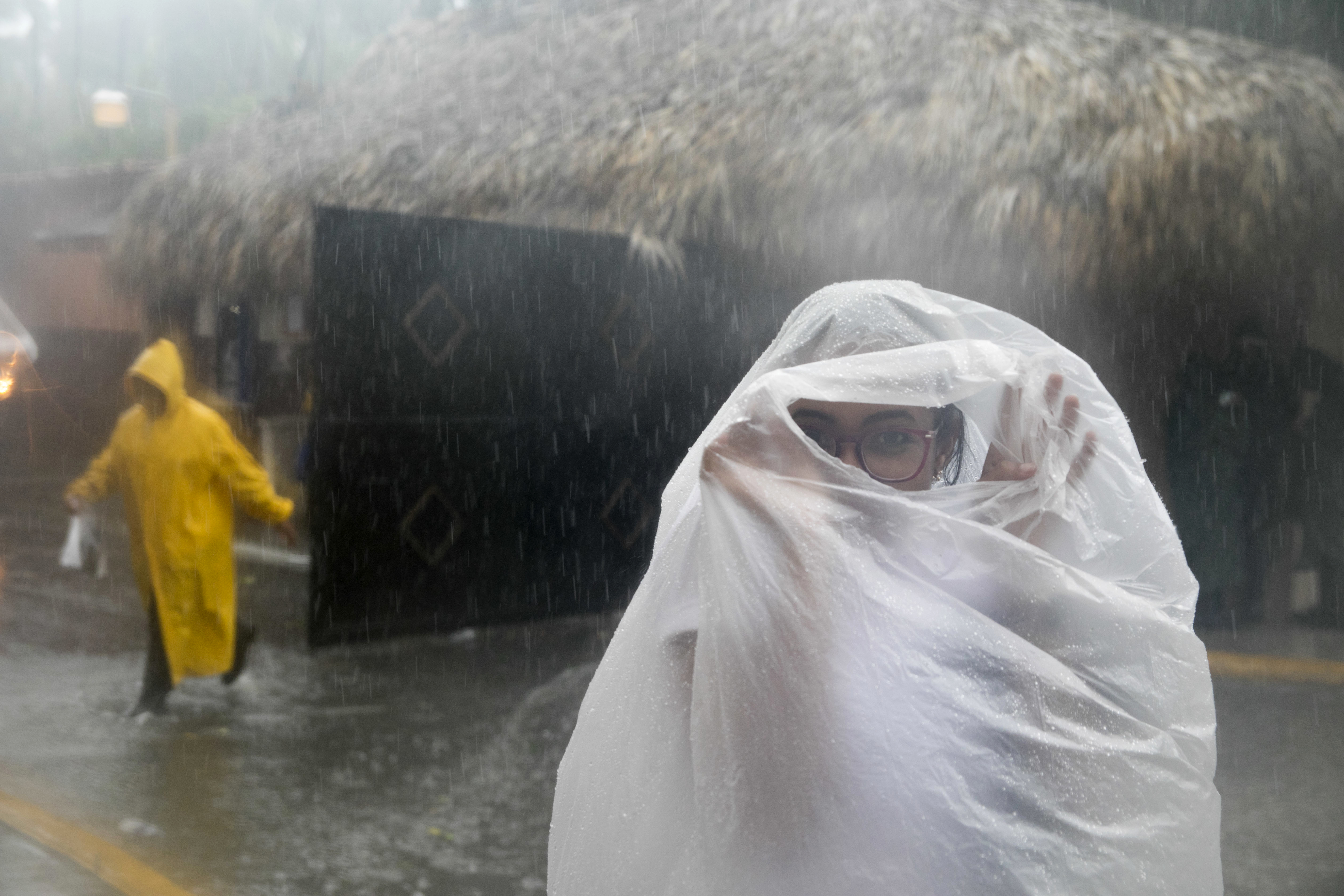 <div class='meta'><div class='origin-logo' data-origin='none'></div><span class='caption-text' data-credit='Tatiana Fernandez/AP Photo'>A woman covers herself with a plastic bag as she makes her way to work as Hurricane Maria approaches the coast of Bavaro, Dominican Republic, Wednesday, Sept. 20, 2017.</span></div>