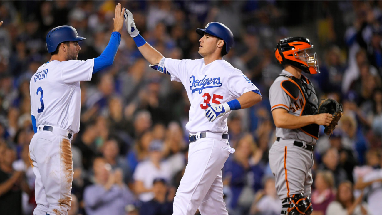 Los Angeles Dodgers' Cody Bellinger, center, is congratulated by Chris Taylor, left, after hitting a three-run home run.