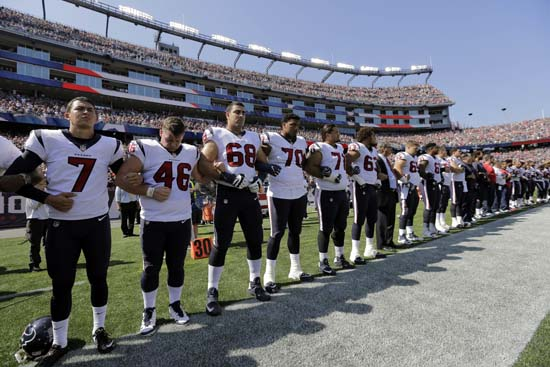 <div class='meta'><div class='origin-logo' data-origin='AP'></div><span class='caption-text' data-credit='Steven Senne'>Members of the Houston Texans team stand with arms locked during the national anthem before an NFL football game against the New England Patriots.</span></div>