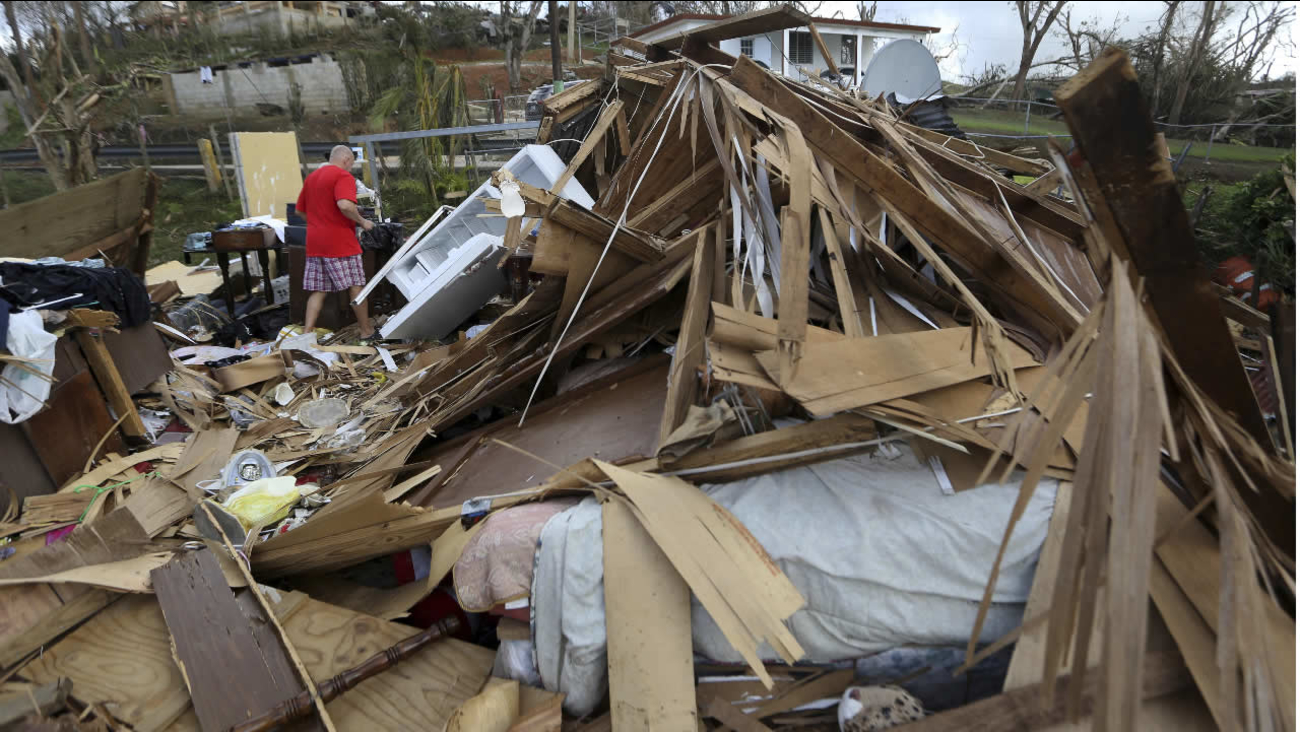 Jose Garcia Vicente walks through rubble of his destroyed home, in the aftermath of Hurricane Maria, in Aibonito, Puerto Rico, Monday, Sept. 25, 2017. (AP Photo/Gerald Herbert)