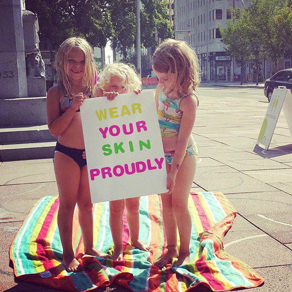 "<div class=""meta image-caption""><div class=""origin-logo origin-image ""><span></span></div><span class=""caption-text"">Three children at the event holding a sign that says ""Wear your skin proudly."" (Kristin Heimbecker / Facebook)</span></div>"