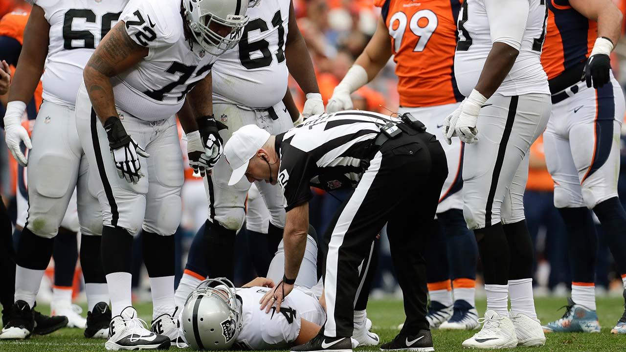 Oakland Raiders quarterback Derek Carr lays the field after being injured during the second half of an NFL football game against the Denver Broncos Sunday, Oct. 1, 2017, in Denver.