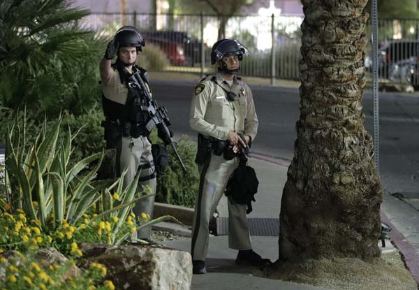 <div class='meta'><div class='origin-logo' data-origin='AP'></div><span class='caption-text' data-credit='AP'>Police officers take cover behind a tree at the Luxor resort and casino during a shooting on the Las Vegas Strip, Sunday, Oct. 1, 2017, in Las Vegas. (AP Photo/John Locher)</span></div>