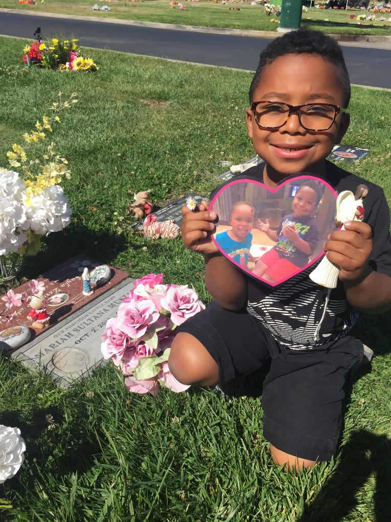 This undated image shows Jeremyah holding up a picture of his sister Mariah, who died in a Stockton, Calif. foster home in 2015 of alleged methamphetamine poisoning.