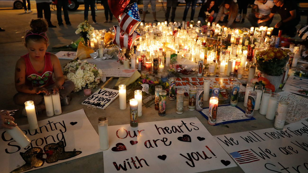 A girl places candles at a memorial for victims of the mass shooting Tuesday, Oct. 3, 2017, in Las Vegas. A gunman opened fire on an outdoor music concert on Sunday.