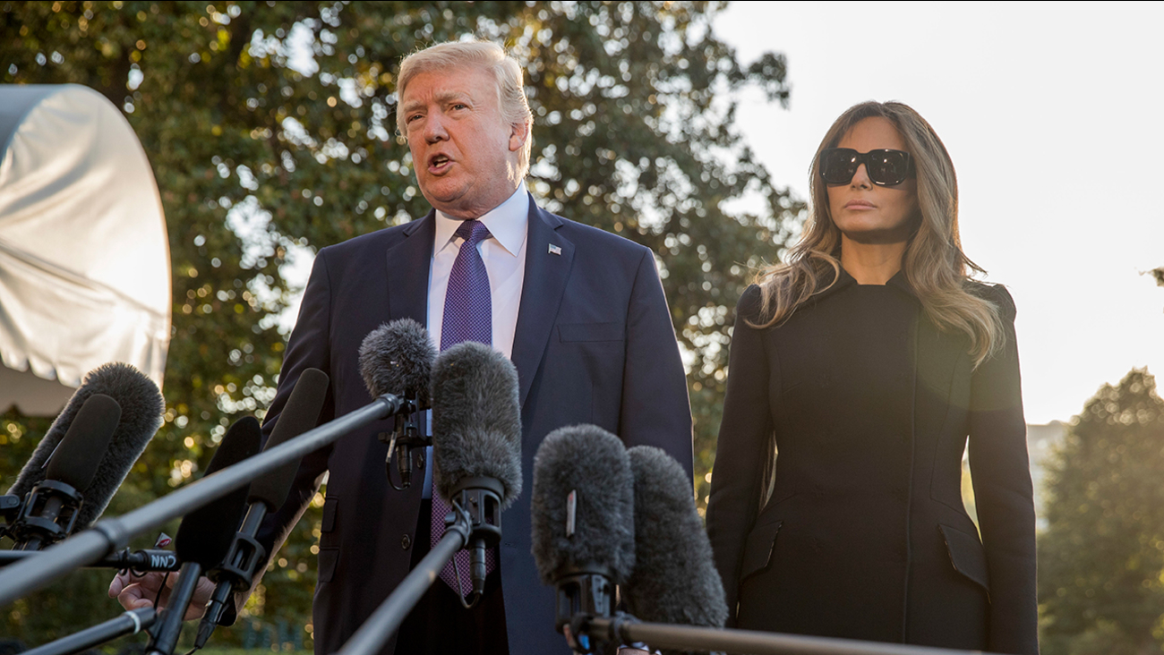 President Donald Trump, accompanied by first lady Melania Trump, speaks to reporters before boarding Marine One on the South Lawn of the White House in Washington, Wednesday, Oct. 4, 2017.