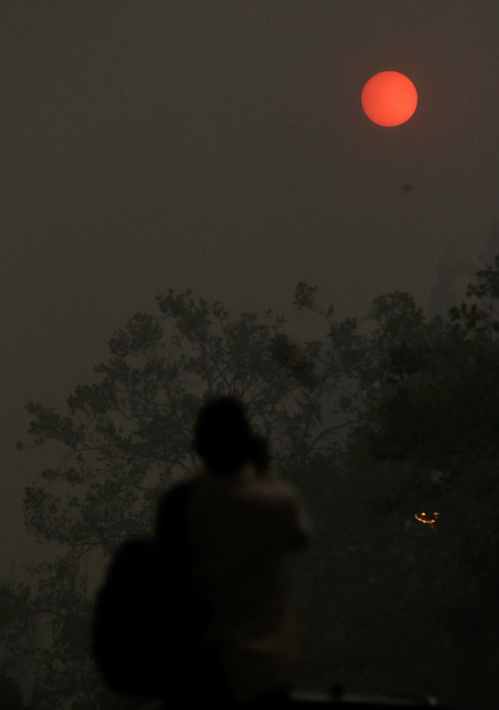 <div class='meta'><div class='origin-logo' data-origin='none'></div><span class='caption-text' data-credit='Jeff Chiu/AP Photo'>A woman takes a photo of the sun covered from smoke and haze from fires in Santa Rosa, Calif., Monday, Oct. 9, 2017.</span></div>