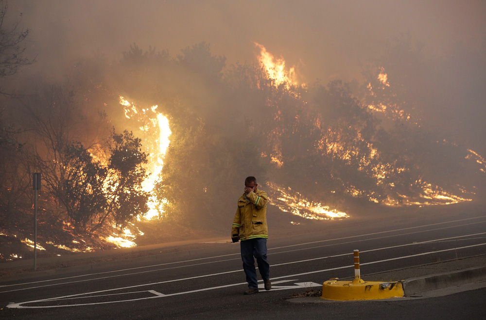 <div class='meta'><div class='origin-logo' data-origin='none'></div><span class='caption-text' data-credit='Jeff Chiu/AP Photo'>A firefighter covers his eyes as he walks past a burning hillside in Santa Rosa, Calif., Monday, Oct. 9, 2017.</span></div>