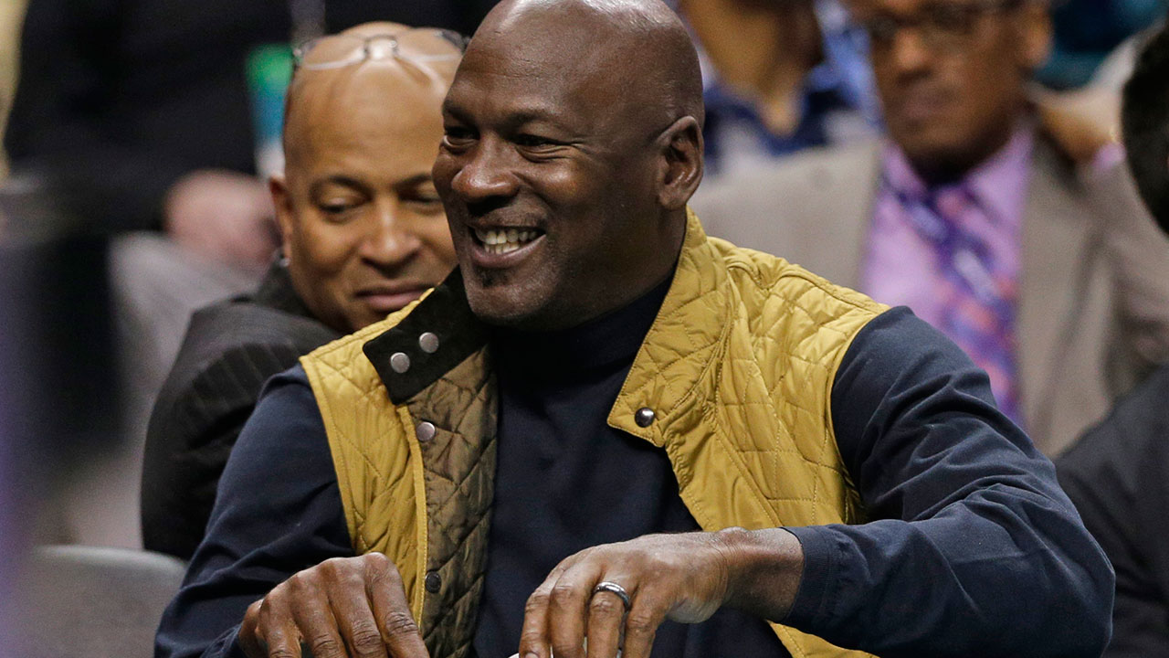 Charlotte Hornets owner Michael Jordan smiles as he watches the action in the first half of an NBA basketball game between the Charlotte Hornets and the Indiana Pacers in Charlotte, N.C., Monday, March 6, 2017. (AP Photo/Chuck Burton)