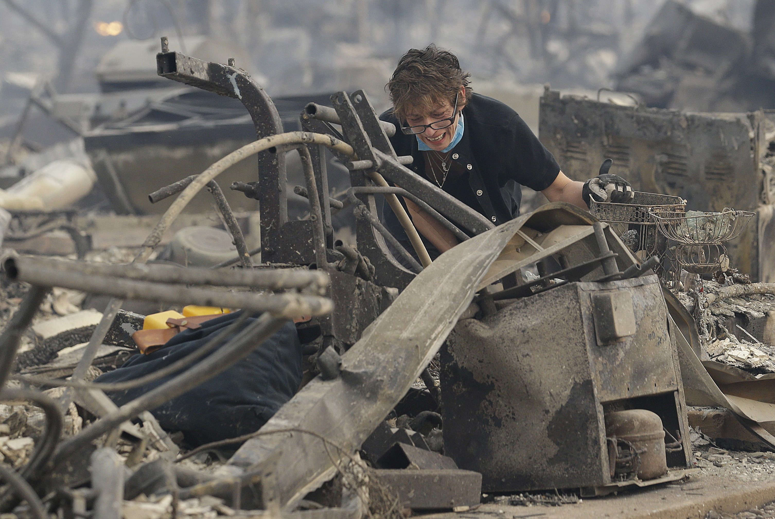 <div class='meta'><div class='origin-logo' data-origin='none'></div><span class='caption-text' data-credit='Jeff Chiu/AP Photo'>Kristine Pond reacts as she searches the remains of her family's home destroyed by fires in Santa Rosa, Calif., Monday, Oct. 9, 2017.</span></div>