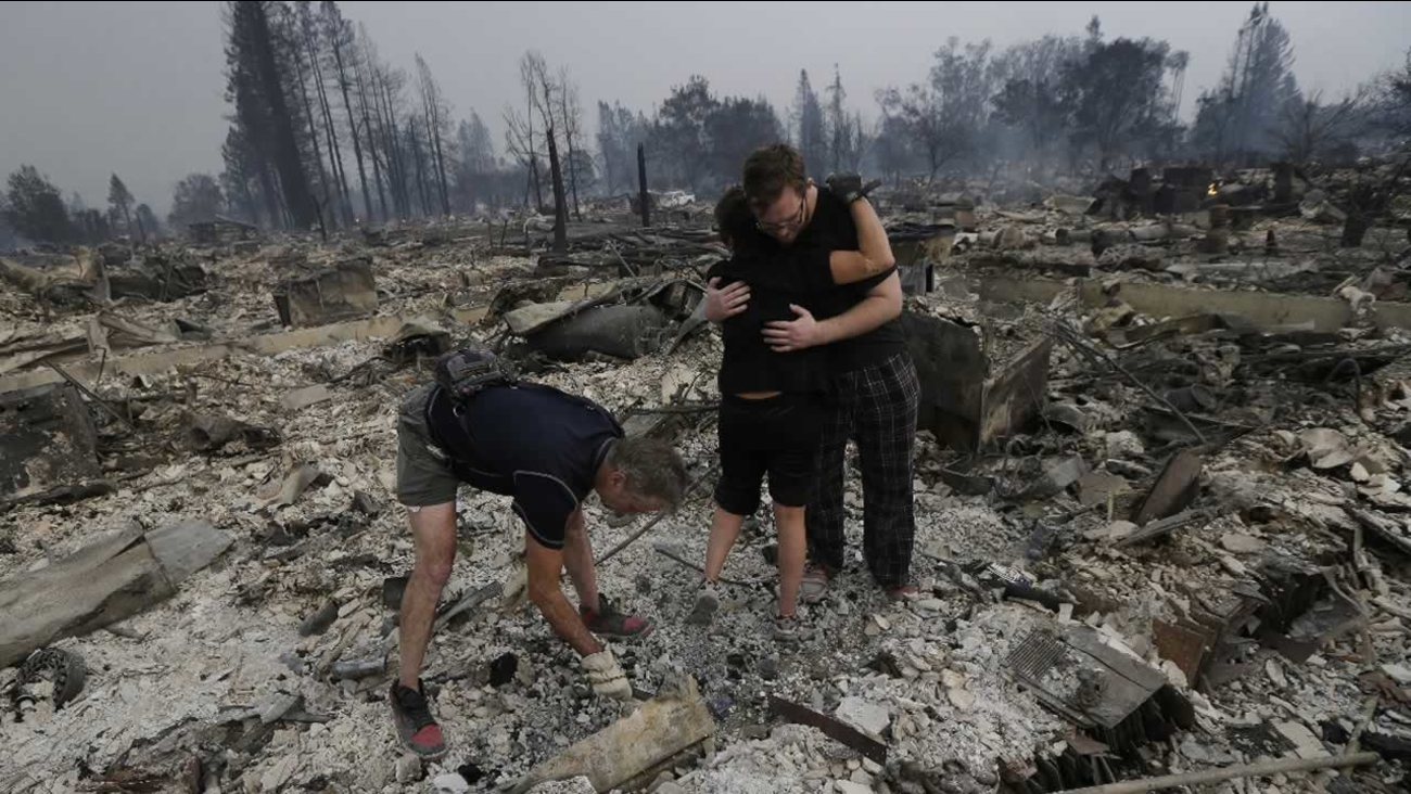 Kristine Pond gets a hug from Zack Thurston while they search the remains of their home destroyed by fires in Santa Rosa, Calif., Monday, Oct. 9, 2017.
