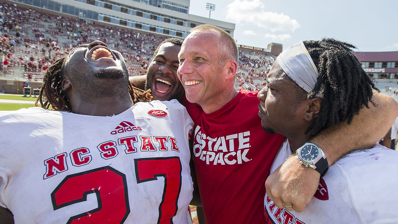 NC State players,Dakwa Nichols (27), defensive tackle B.J. Hill, head coach Dave Doeren and linebacker Jerod Fernandez celebrate defeating Florida State 27-21 on Sept. 23.