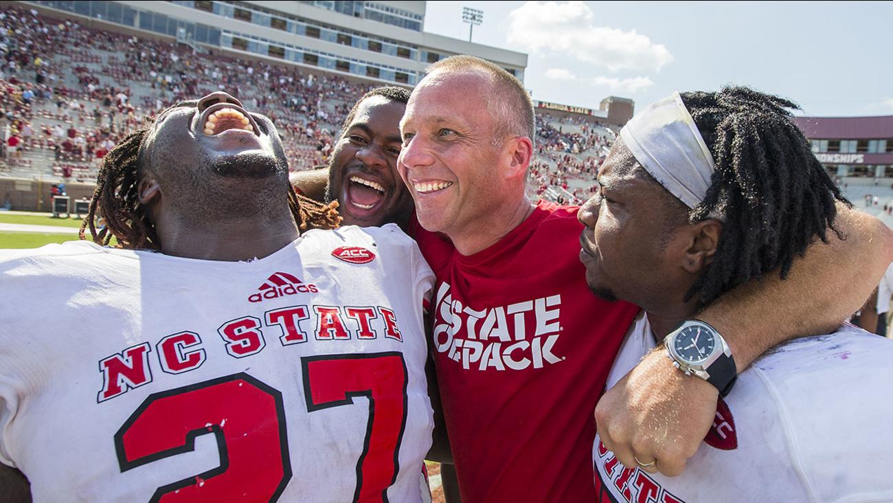 NC State players,Dakwa Nichols (27), defensive tackle B.J. Hill, head coach Dave Doeren and linebacker Jerod Fernandez celebrate defeating Florida State 27-21 on Sept. 23.