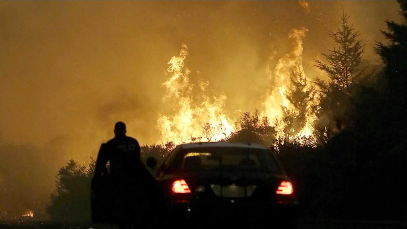 A law enforcement officer blocks a road as flames from a wildfire burn in a residential area in Santa Rosa, Calif., Monday, Oct. 9, 2017.