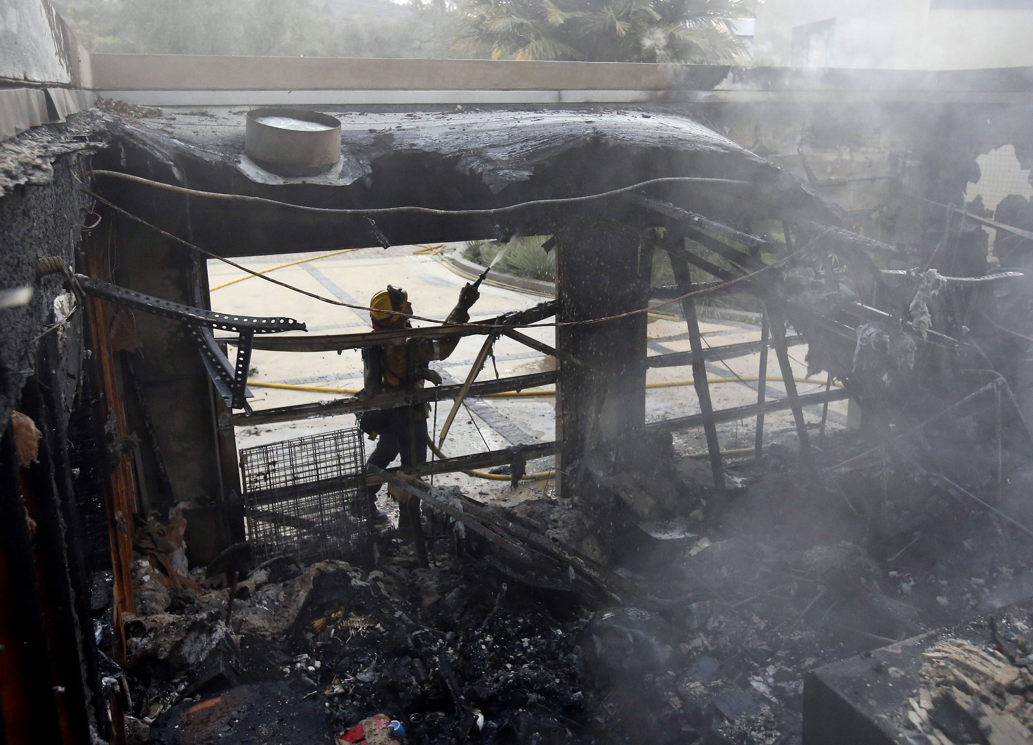 <div class='meta'><div class='origin-logo' data-origin='none'></div><span class='caption-text' data-credit='Rich Pedroncelli/AP Photo'>Firefighter Nick Gonzalez-Pomo, of the San Rafael Fire Department, waters down hot spots on a garage Tuesday, Oct. 10, 2017, in Napa, Calif.</span></div>