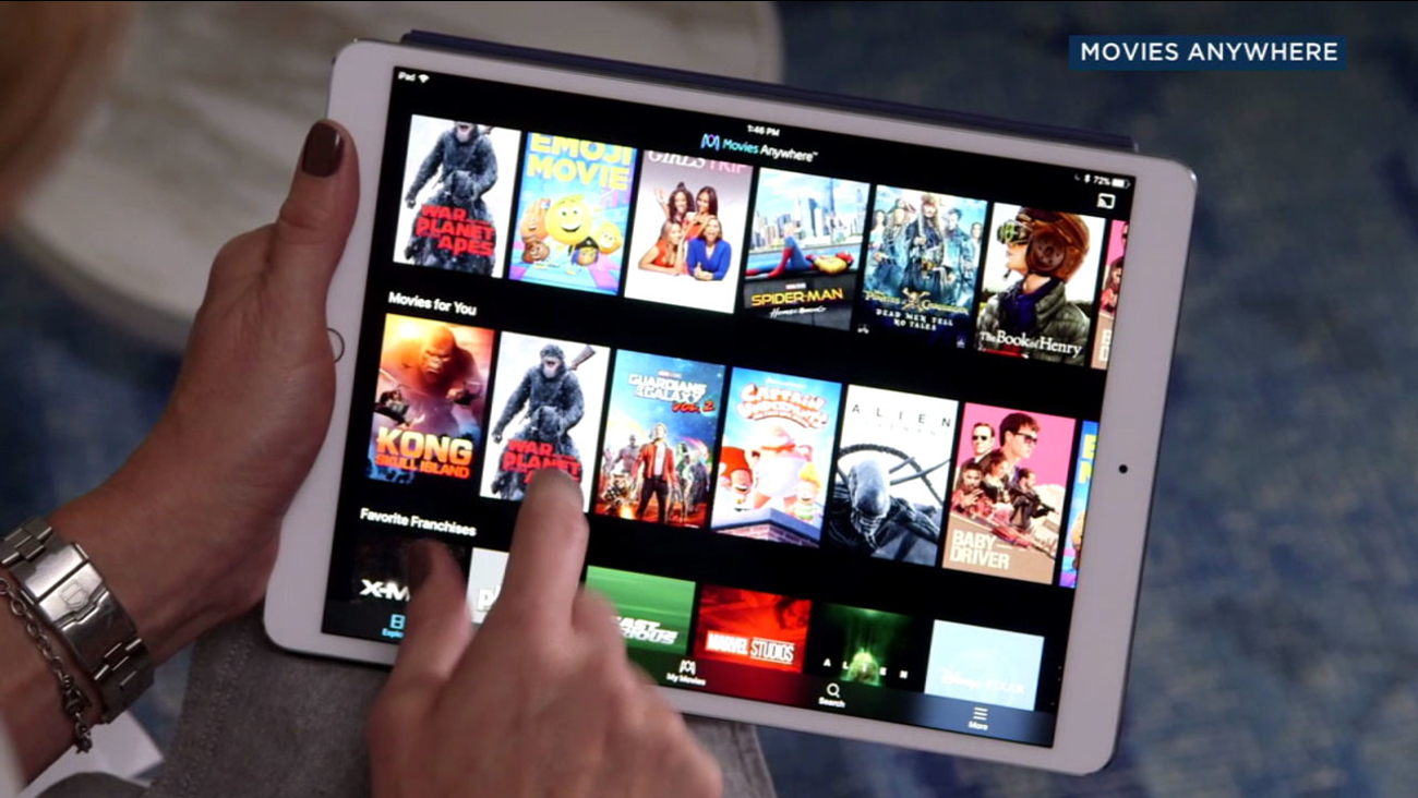 "A woman swipes through the ""Movies Anywhere"" app on a tablet."