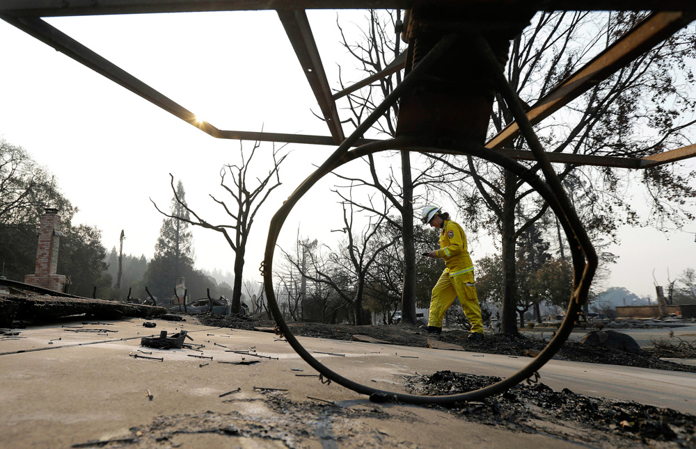 <div class='meta'><div class='origin-logo' data-origin='none'></div><span class='caption-text' data-credit='Jeff Chiu/AP Photo'>Cal Fire forester Kim Sone is framed by a fallen basketball hoop as she inspects damage at homes destroyed by wildfires in Santa Rosa, Calif., Thursday, Oct. 12, 2017.</span></div>