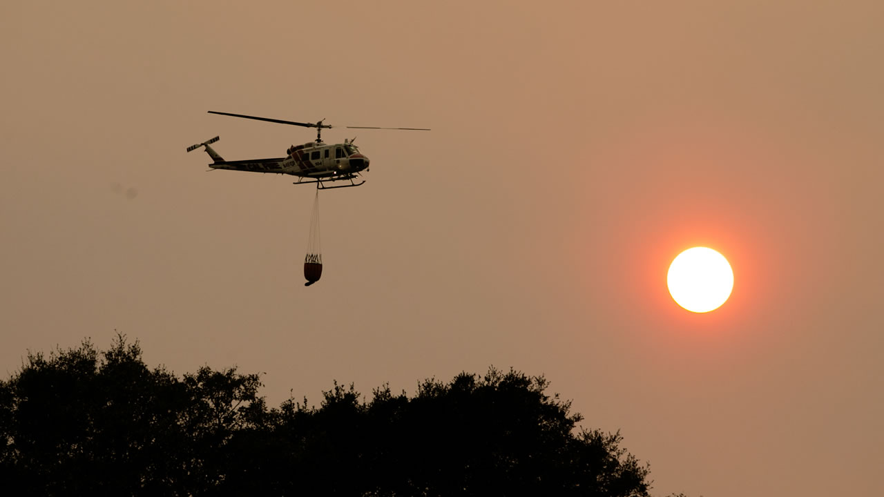 A helicopter flies through the smokey sky to drop a load of water on a wildfire Thursday, Oct. 12, 2017, in Sonoma, Calif.