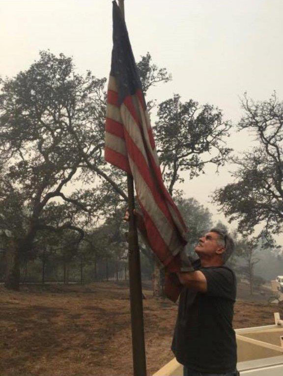 <div class='meta'><div class='origin-logo' data-origin='none'></div><span class='caption-text' data-credit='Danielle Funez'>A man raises the American flag at his home that was burned down during the wildfires.</span></div>