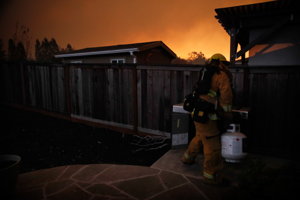 <div class='meta'><div class='origin-logo' data-origin='none'></div><span class='caption-text' data-credit='Jae C. Hong/AP Photo'>A firefighter removes a propane gas tank in an evacuated residential area as wildfires continue to burn Saturday, Oct. 14, 2017, in Santa Rosa, Calif.</span></div>