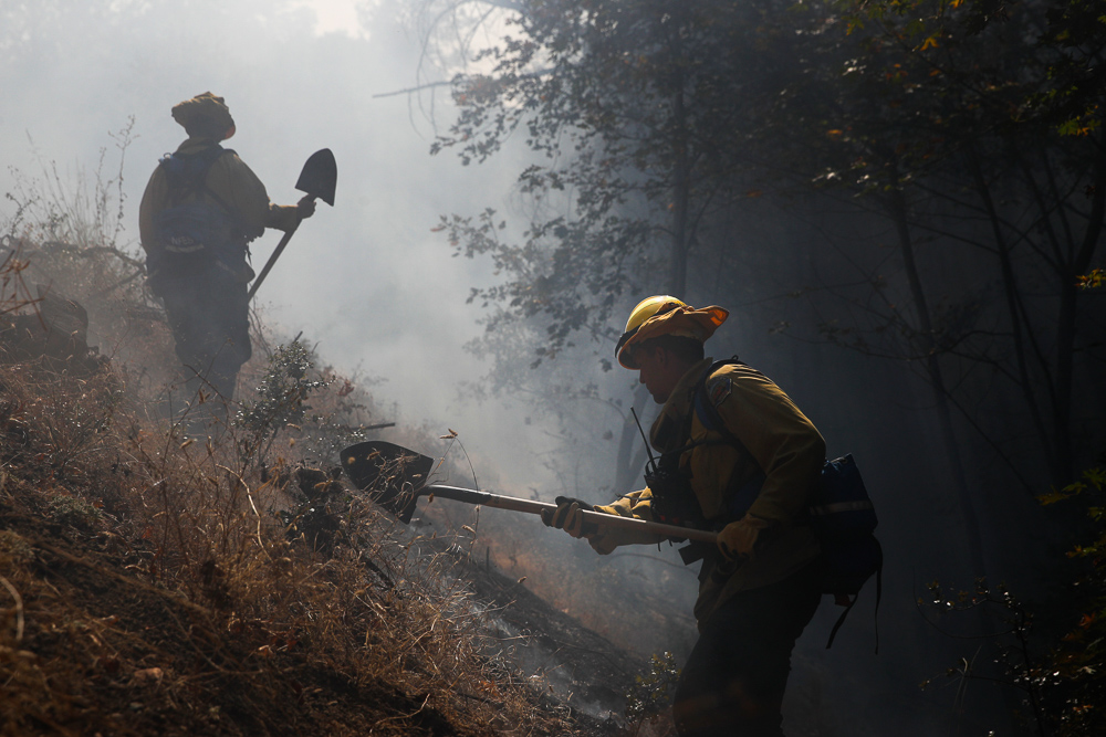 <div class='meta'><div class='origin-logo' data-origin='none'></div><span class='caption-text' data-credit='Jae C. Hong/AP Photo'>Firefighter Robert Elliott, right, cuts a line to prevent a wildfire from jumping to the other side of the road Friday, Oct. 13, 2017, near Calistoga, Calif.</span></div>